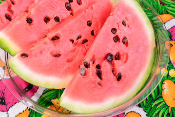 Cut pieces of ripe watermelon on a plate close-up.