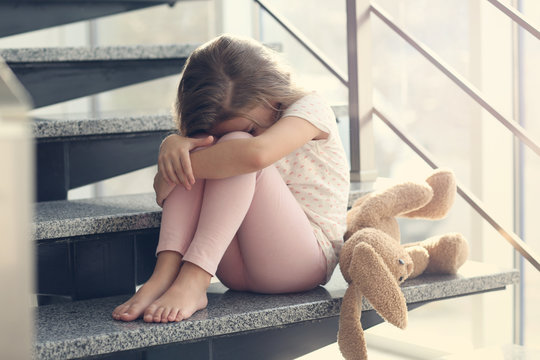 Sad little girl sitting on stairs