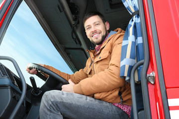 Driver in cabin of big modern truck