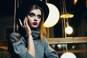 Portrait of a young beautiful fashionable woman touching her face, looking forward. Girl sitting in cafeteria. Model wearing stylish turtleneck and wide-brimmed hat. Close up. Female fashion concept