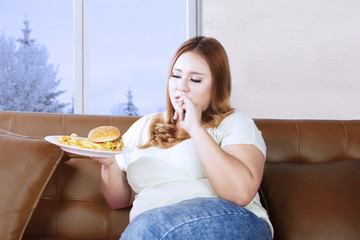 Obese woman enjoying junk food at home