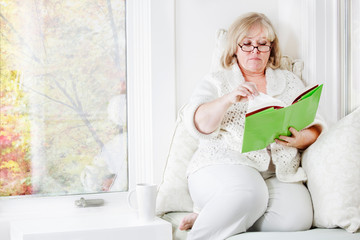 Older woman curled up in a window seat, reading a good book