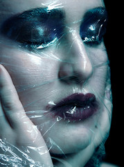Halloween beauty portrait of young woman covered by polyethylene