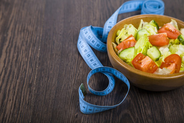 Salad in wooden bowl and measuring tape on a dark table close-up