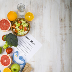 Food and sheet of paper with a diet plan on a  wooden table. Con