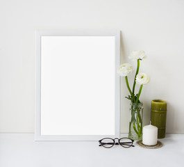 Empty white frame mockup for design presentation, promotional or art content and ranunculus bouquet in glass vase, candles and glasses. Light romantic style concept, minimalism design.