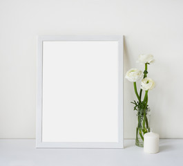 Empty white frame with place for text on the white wall and table, bouquet of flowers ranunculus and candle. Scandinavian style room interior. Template mock up for paintings or photographs