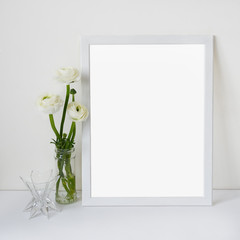White wooden frame with place for text with ranunculus bouquet in glass vase on a background of a white wall and table. Light romantic style concept, minimalism design