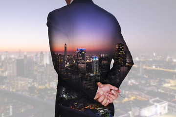 Double exposure of businessman think and analyze the work, cityscape, urban and street in the night or twilight as vision of leader concept.