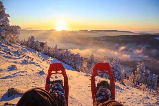 Winter sport activity concept. Hiker looking over his snowshoes at the beautiful landscape in the French mountains during sunset.