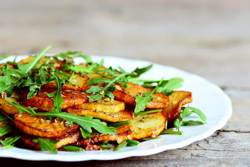 Roasted potatoes with arugula. Combine fresh arugula mixture and hot potatoes on a white plate. Delicious and healthy recipe. Closeup