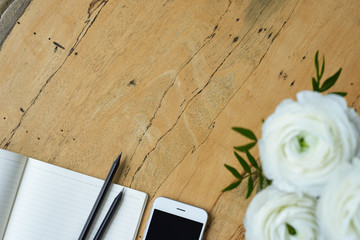 Top view of blank notepad, mpbile phone, black pencils and bouquet of white flowers ranunculus on a solid wooden desk. Background for your promotional content. Focus on flower.