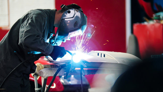 Welding industrial: worker in helmet repair detail in car auto service - blue sparklers