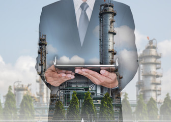 Double exposure of business man hand hold tablet and  Electric Generating Factory at the day as Energy and Technology concept.
