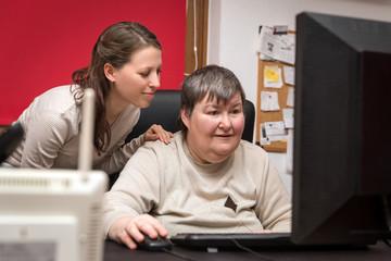 Betreuerin und geistig behinderte Frau lernen am Computer