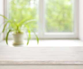 Light wooden table on defocuced summer window background