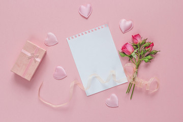 Blank page notepad with small roses, gift box and hearts on a pi