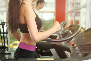 Young sporty woman running on treadmill in gym, close up view
