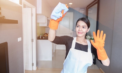 Asian young maid cleaning the mirror at home, Cleaning service concept