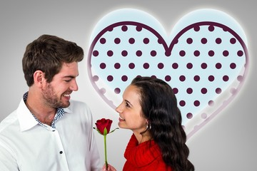Composite image of smiling couple holding rose
