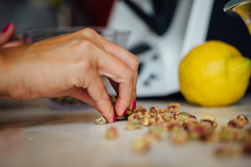 Woman taking peeled pistachio