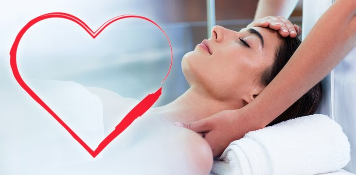Composite image of head massage on woman with love heart