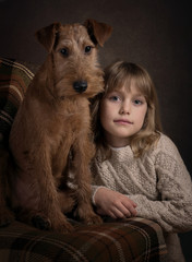 Portrait of serious little girl and the Irish terrier puppy on the dark studio background