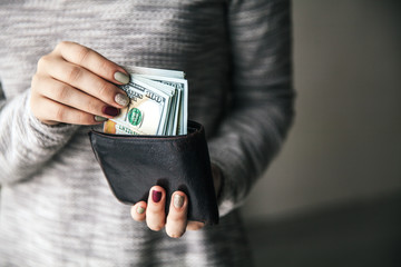 In the women's hands is the leather wallet with a wad of hundred dollars. Business offer. Beautiful manicure
