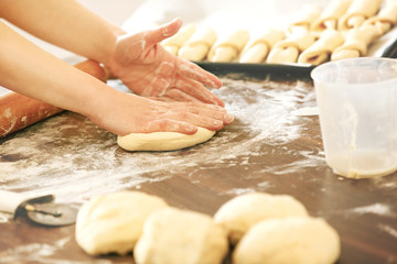 Woman in the kitchen preparing croissants to bake.