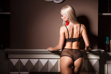 Perfect, sexy body and ass of young blonde woman wearing seductive lingerie. Beautiful hot female in underware posing on sensual way in luxury interior.