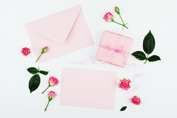 Gift or present box, envelope, paper blank and pink rose flower on white table top view in flat lay style for greeting card on Womans day.