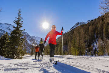 A family group of cross country skiers on a sunny winter morning