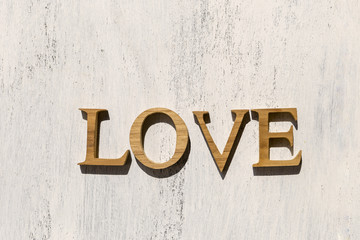 Wooden love sign on white wood background, outdoor day light