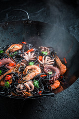 Spicy spaghetti with seafood with shrimp and octopus in wok