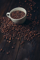Coffee beans on a wooden background and in a white cup, top view
