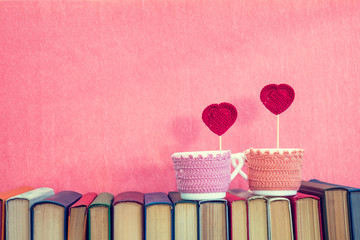 Valentines day concept. Two cups with red crochet hearts on books over pink background.