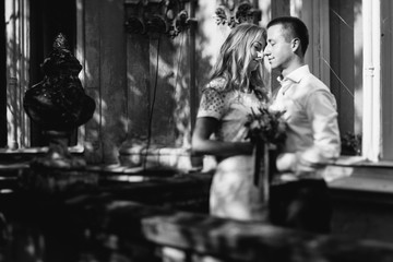 Tender hugs of beautiful wedding couple standing in the shadows on balcony