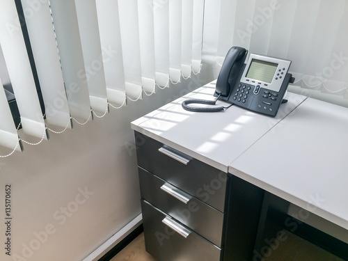 Black office phone on white empty desk in office room with window ...