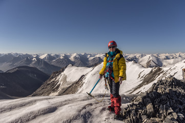 girl in the mountains at the top in the equipment, climber