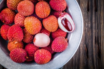 Fresh organic lychee fruit in a bowl on wooden background. Top view