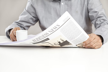 Man reading newspaper on table