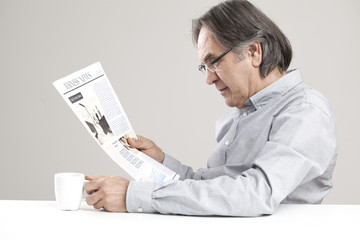 Senior man reading newspaper on gray background