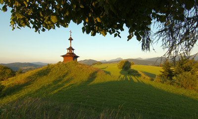 View of a meadow with a small chapel and mountains  in Slovakia