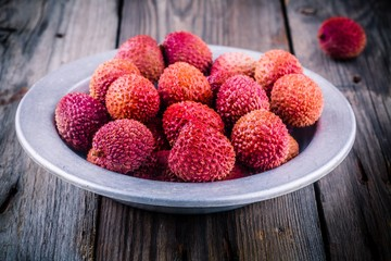 Fresh organic lychee fruit in a bowl on wooden background