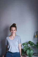 Junge Frau mit Haaknoten in ihrer Wohnung