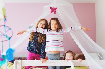 Three little girls playing in kid's room