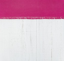 Red fabric napkin on the background of white wooden wall