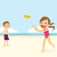 Two cute little kids playing flying disk at beach on summer holiday