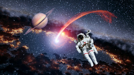 Astronaut planet Saturn spaceman comet outer space suit galaxy universe. Elements of this image furnished by NASA.