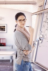 Casual female architect standing at drawing board